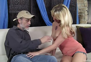 Small tits blonde enjoys having sex anent an older alms-man on the sofa